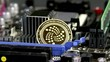 IOTA token leaning on the cooling fins of a motherboard. The setup is placed on a rotating turntable with a light source that is reflected by the coin during rotation.