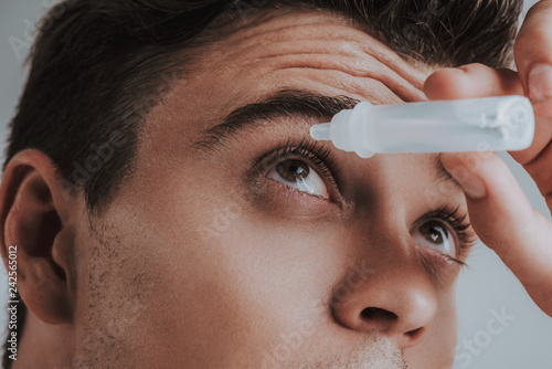 Foto Murales Close up of young man carefully using eye drops