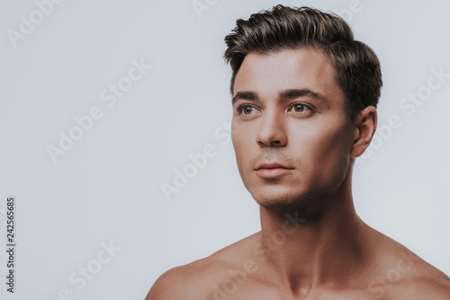 Portrait of young dark haired man looking into the distance