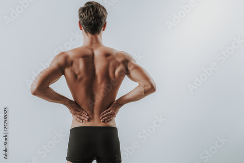 Waist up of muscular man putting hands on the back
