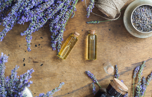 lavender oil bottles,  natural herb cosmetic consept with lavender flowers flatlay on stone background - 242565824