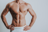 Muscular topless man posing with hands on the hips - 242566097