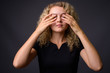 Young beautiful woman with curly blond hair covering eyes