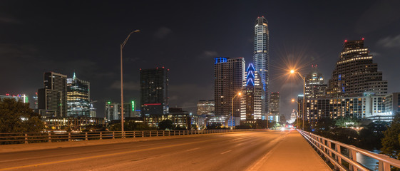Panorama view downtown Austin at night with traffic light trail lead to Texas State capitol building. View from pedestrian sidewalk on bridge across Colorado River