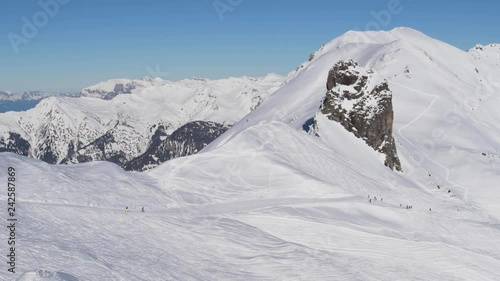 A bunch of skier and snowboarder passing a big and imposing rock in the Swiss Alps. This ski resort is called Arosa-Lenzerheide and is located in Arosa, Switzerland.
