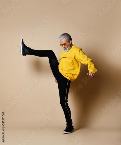 Leinwanddruck Bild senior millionaire man in yellow cloth and aviator stylish sunglasses exercise stretching hit punch with leg
