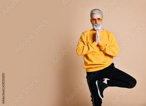 Leinwanddruck Bild Portrait of happy senior millionaire man in yellow sunglasses stylish fashionable men practicing yoga asana stretching exercise