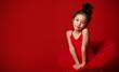 Leinwanddruck Bild - Cute little girl ballerina in beautiful dress is dancing on red