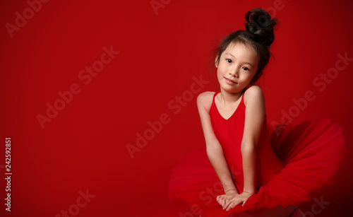 Leinwanddruck Bild Cute little girl ballerina in beautiful dress is dancing on red