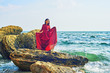 a young girl on the sea coast, a girl in a red dress resting sitting on the rocks