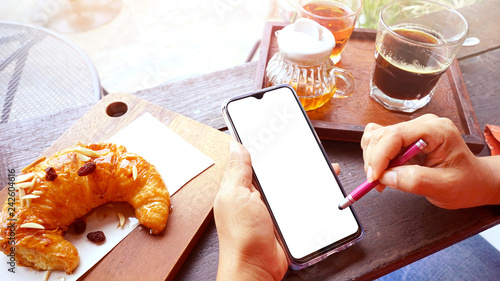 Lady using smart phone on coffee table in cafe , White screen in smart phone    - 242604616