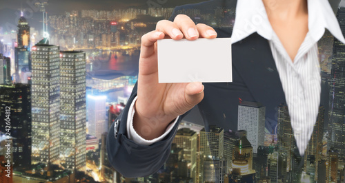 Businessman's hand holding blank cardboard, in front with blur building background.