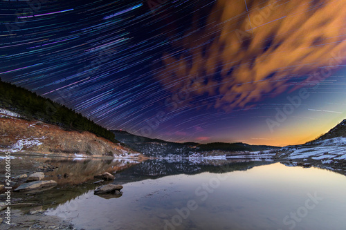 Star trails over lake - 242606065