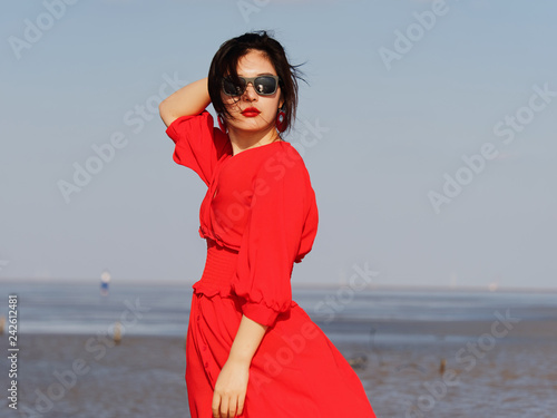 a85b37962e1d Sexy Chinese young girl in red dress posing on sunny beach with black long  hair in