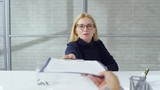 POV shot of mature woman with blond hair talking and giving skills assessment test to applicant during job interview - 242613249