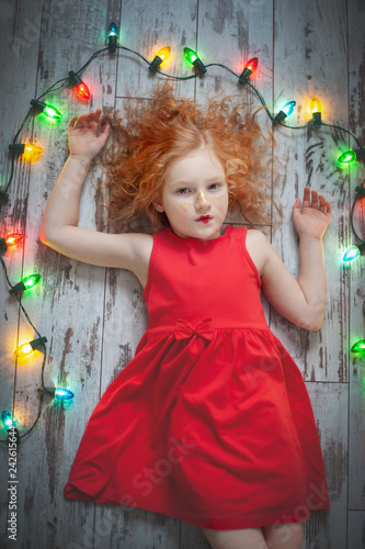 Foto Murales Curly red-haired girl in a red dress lying with a garland