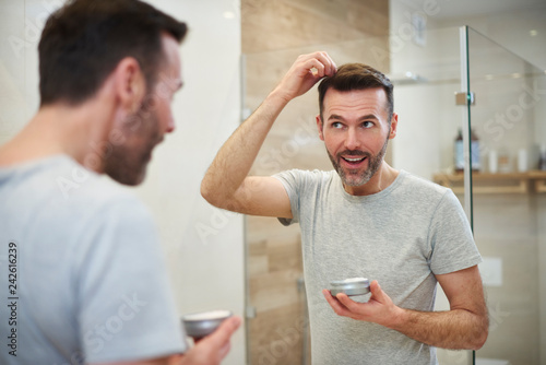 Leinwandbild Motiv Mature man applying hair gel in the bathroom