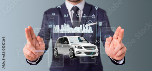 Businessman holding Dashboard smartcar interface with multimedia icon and city map on a background 3d rendering - 242621264