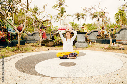 Young woman practicing yoga - meditation in the tropical garden with yin yang sign.