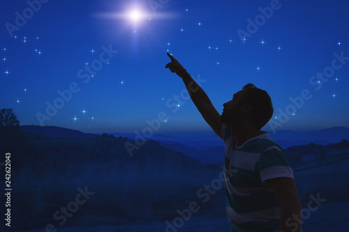 Man pointing at the starry night sky. Elements of this image are my work.