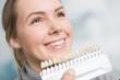 Bei einer jungen Frau wird die Zahnfarbe mit einer Zanfarbprobe ermittelt