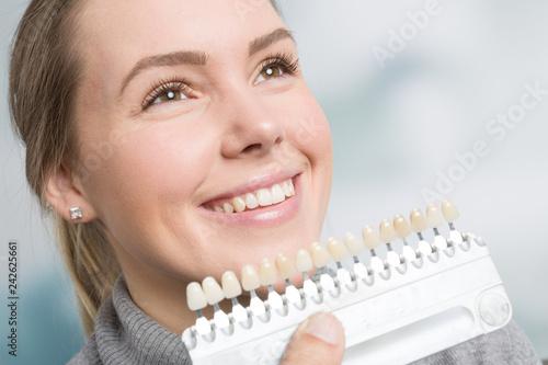 Bei einer jungen Frau wird die Zahnfarbe mit einer Zanfarbprobe ermittelt - 242625661