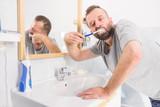 Man brushing his teeth in bathroom - 242625827
