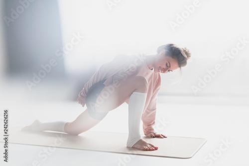 Smiling woman training yoga asana on mat