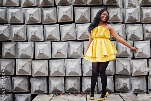 Stylish african american woman at yellow dress posed against stone texture background.