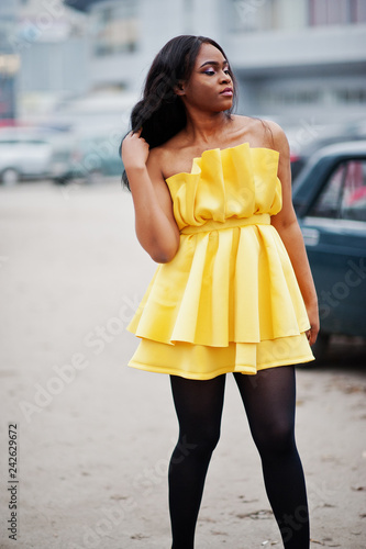 Stylish african american woman at yellow dress posed outdoor car parking.
