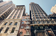 Looking up at old New York buildings, color toned picture with a lens flare, USA.