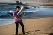 Musician play to tuba on the Sea shore.
