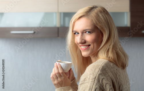 Close-up portrait of a beautiful mid age woman with cup of coffee.