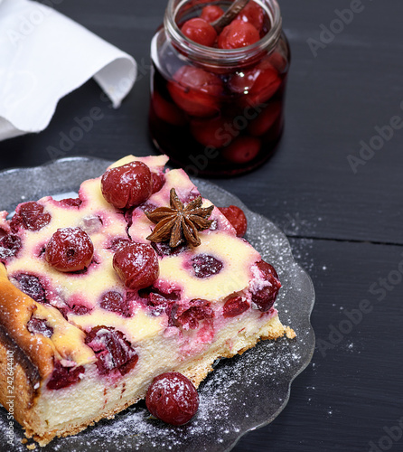 piece of a cheesecake with cherries on a glass plate