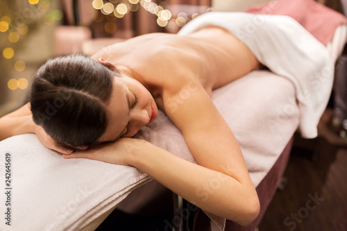 people, beauty, healthy lifestyle and relaxation concept - young woman lying at spa or massage parlor