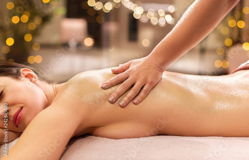 people, beauty, healthy lifestyle and relaxation concept - beautiful young woman lying and having back massage at spa