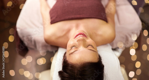 people, beauty, healthy lifestyle and relaxation concept - happy young woman lying at spa or massage parlor