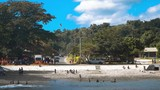 People are swimming and relaxing on a public beach on the main street in Lanakel city, Tanna island, Vanuatu. - 242649258
