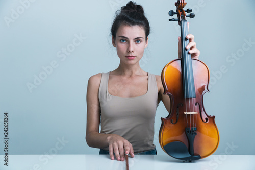 Portrait of a beautiful young woman sitting at the table - 242651264