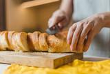 Female European hands cut fresh crisp baguette on wooden board