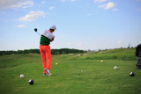 man playing golf on a green field. Professional sports
