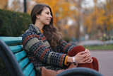 Pretty young woman sitting on a bench enjoying the good weather. - 242661079