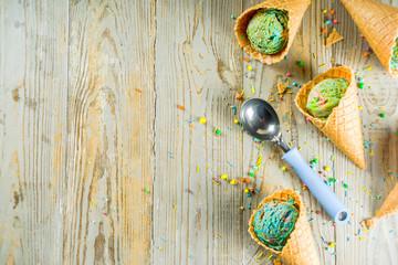 Multicolored rainbow ice cream with icecream cones on wooden background