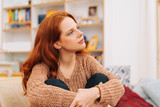 Young woman sitting thinking or planning - 242663051