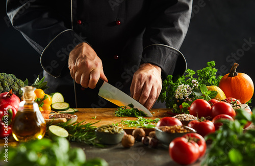 Chef dicing fresh herbs with a kitchen knife