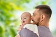 family, parenthood and people concept - father with little baby daughter over green natural background - 242663622