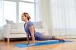 Leinwanddruck Bild - fitness, sport and healthy lifestyle concept - woman doing yoga upward-facing dog pose on mat at home