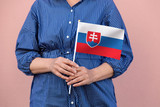 Slovakia flag. Close up of a woman's hands holding Slovakian flag.