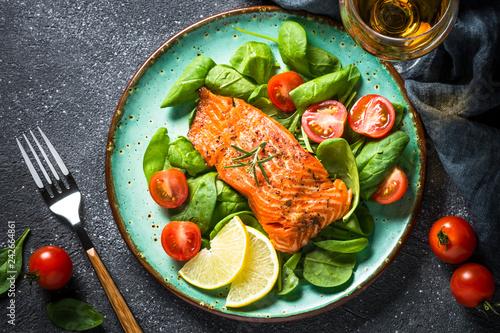 Leinwanddruck Bild Baked salmon fish fillet with fresh salad top view.