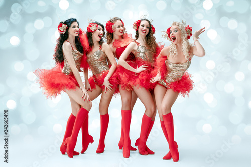 The group of young happy smiling beautiful female dancers with carnival dresses posing on blue studio background - 242665498